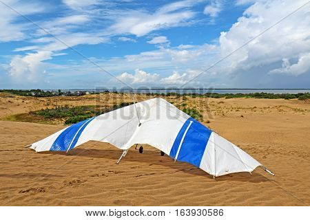 Hang glider on the sand of Jockeys Ridge State Park in Nags Head on the Outer Banks of North Carolina with dramatic clouds dunes and Albemarle Sound in the background