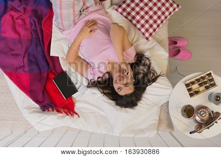 Woman In Bed With Phone