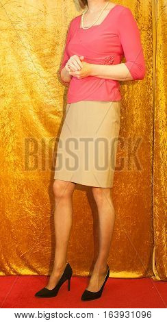 Woman wearing high heel stilettos, skirt and top stood by curtain.
