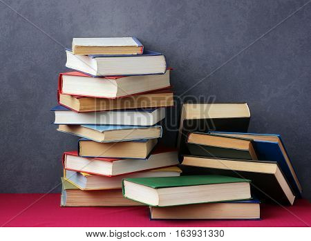 Stack of books in the colored covers on the table with a red tablecloth. Still life with books.