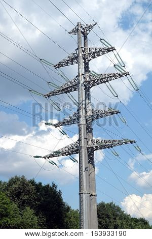 Country landscape with high-voltage power line grey metal prop with many wires in summer day