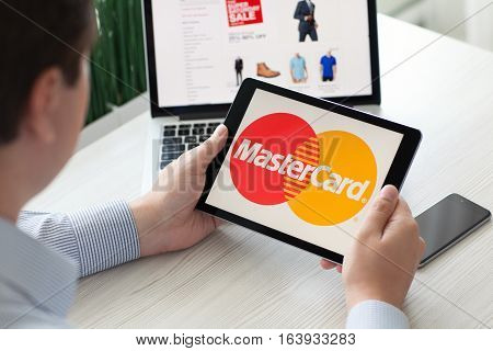 Alushta Russia - September 3 2016: Man holding a iPad Pro with payment system service MasterCard on the screen. iPad Pro was created and developed by the Apple inc.