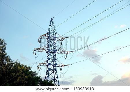 High-voltage power line metal pylon with wires over cloudy blue sky on the sunset horizontal view