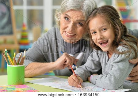 Portrait of grandmother and granddaughter drawing together