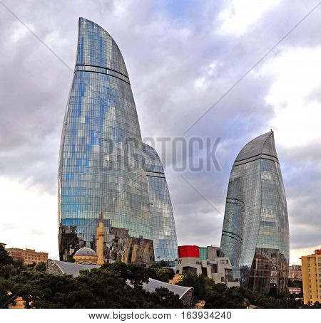 BAKU AZERBAIJAN - SEPTEMBER 25: Martyrs mosque in front of Flame towers in Baku on September 25 2016. Baku is a capital and largest city of Azerbaijan.