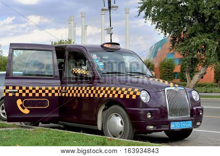 BAKU AZERBAIJAN - SEPTEMBER 25: Purple taxi cab in the street of Baku on September 25 2016. Baku is a capital and largest city of Azerbaijan.