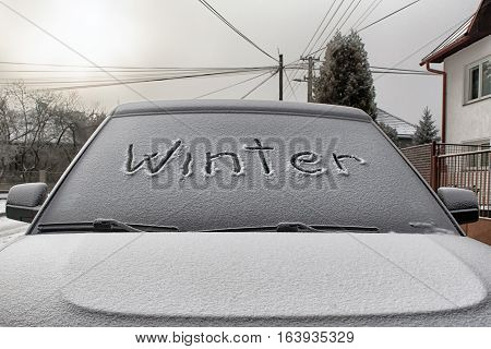 Text WINTER on windshield of car in city