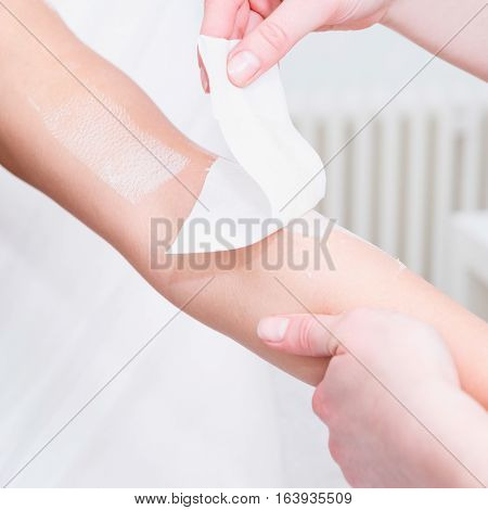 Waxing woman's arm in beauty salon, toned image