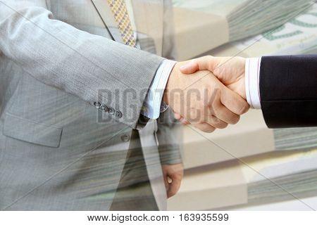 Closeup of handshake on bundles of banknotes background