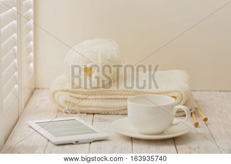 Knitting e-book and a cup on a light wooden background near a window with shutters.
