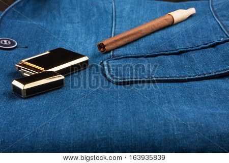 Cigar and gold lighter lying on a blue denim jacket with space for your text