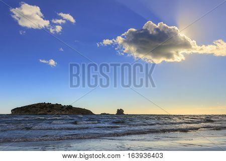 Gargano coast: Portonuovo beach,Vieste-(Apulia) ITALY-Islet between waves dominated by cloud crossed by sunbeams.