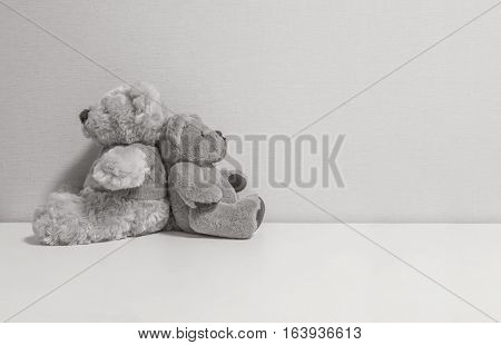 Closeup couple of bear doll on white desk and wall textured background in black and white tone with copy space