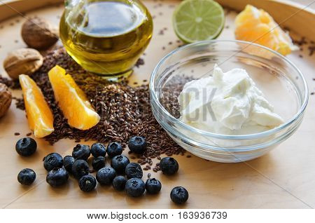 Healthy breakfast muesli with quark or cottage cheese flax seeds linseed oil and fresh fruits on a wooden board budwig diet