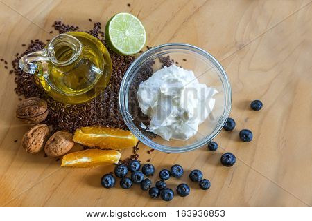 Healthy breakfast with quark or cottage cheese flax seeds linseed oil and fresh fruits on a wooden board view from above budwig diet