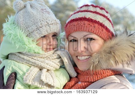 mother with daughter posing outdoors in winter