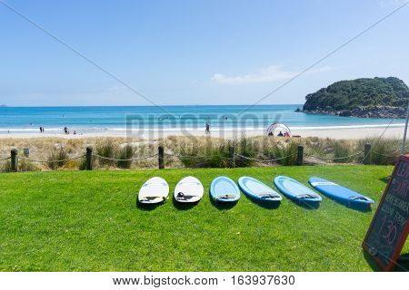 Mount Maunganui, New Zealand - December 21, 2016: Mount Maunganui ocean-beach with people enjoying summer and beach activities with line of hire surfboards lying on grassy edge to beach
