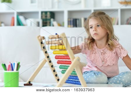 Portrait of a little girl counting doing homework