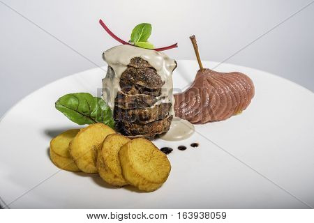 Grilled fillet mignon with potatoes and pear boiled in wine