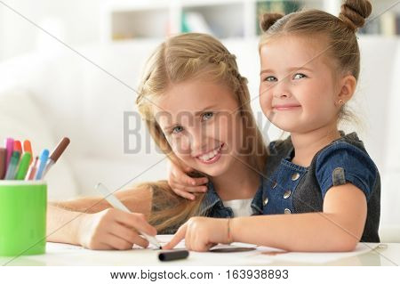 Portrait of two cute sisters drawing and smiling
