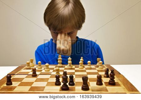 Serious clever boy looking at chess board and thinking about next move. Game education concept