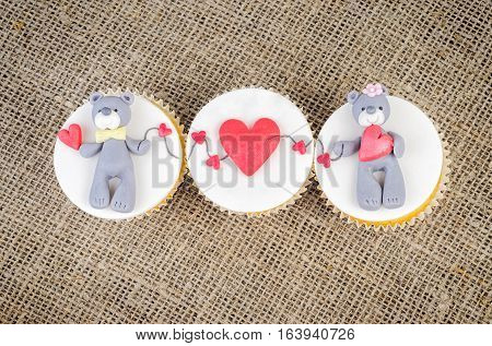 Cupcakes with teddy bear and hearts on on rustic jute background. Valentine's Day cupcake.