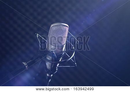 Microphone and audio console in holder isolated on dark background in rays of light stream in recording studio