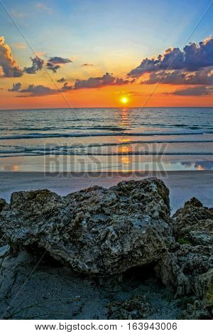 A sunset over the ocean with rocks