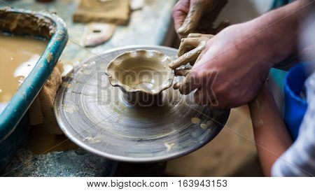Senior potter teaching a little boy the art of pottery. Child working with clay Creating ceramic pot on sculpting wheel. Concept of mentorship mentoring generations. Arts lessons pottery workshop for kids