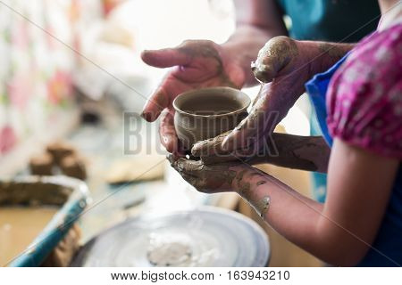 Senior potter teaching a little girl the art of pottery. Child working with clay Creating ceramic pot on sculpting wheel. Concept of mentorship generations. Arts lessons pottery workshop for kids