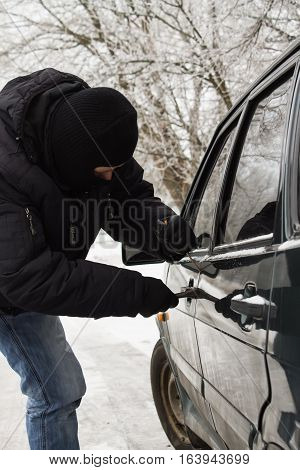 criminal in a mask hijacks auto. Opening the car lock. Vertical photo
