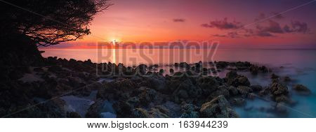 Beautiful vivid sunset over beach reef in Indian ocean Maldives panorama