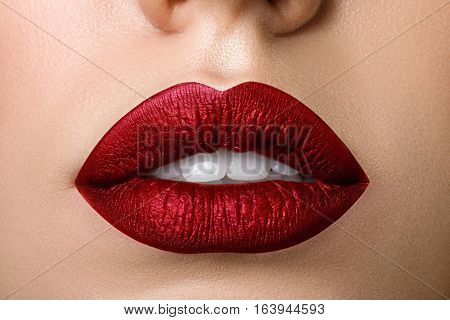Close up view of beautiful woman lips with purple matt lipstick. Open mouth with white teeth. Cosmetology drugstore or fashion makeup concept. Beauty studio shot.