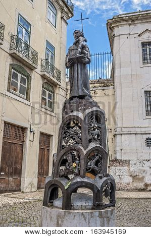 Lisbon Portugal. Sculpture in front of Santo Antonio Church bright spring day a beautiful yellow rose on a pedestal.