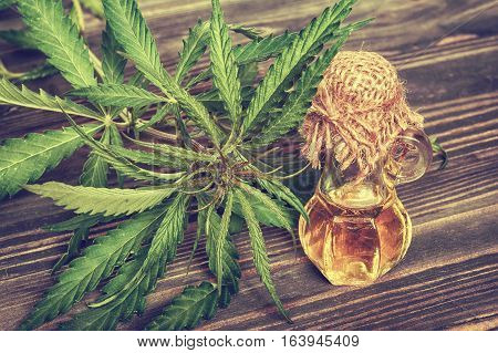 Cannabis leaves and oil in glass bottle on wooden background. Vintage toned