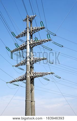 Tall High-voltage power line grey metal prop with many wires vertical view over clear cloudless blue sky bottom-up view