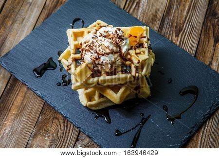 Viennese waffles with chocolate, mandarine and ice-cream on blackboard