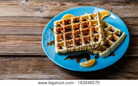 Viennese waffles on blue plate on wooden table with tangerines