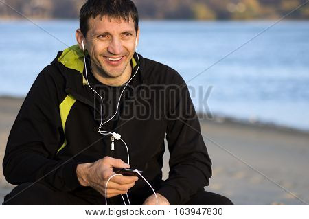 Smiling man with earphones is sitting outdoors along the riverside.