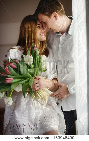Young man congratulates his woman. She sits in a beautiful white dress with a bouquet of multi-coloured tulips. Man tenderly embracing girlfriend and lovingly looks at her.