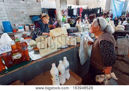 SIGNAGI, GEORGIA - OCT 7, 2016: Older women buying homemade cheese on Georgian village market on October 7, 2016. Signagi of Kakhetia has a population 2.200