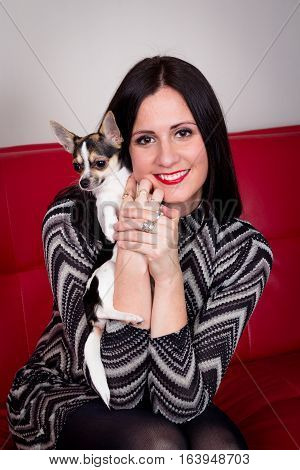 luxurious young women model on red couch with chihuahua