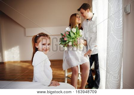 Young man congratulates his pregnant wife. She sits in a beautiful white dress with a bouquet of tulips. Husband gently hugs a wife and lovingly looks at her. Little daughter looks in the camera.