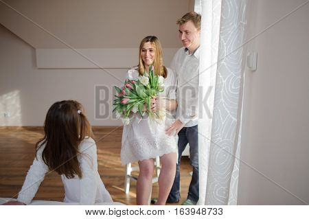 Young man congratulates his pregnant wife. She sits in a beautiful white dress with a bouquet of tulips. Husband gently hugs a wife and lovingly looks at her. Little daughter looks at the parents.