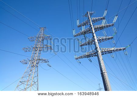 High-voltage power line grey metal props with many wires vertical view over clear cloudless blue sky bottom-up view