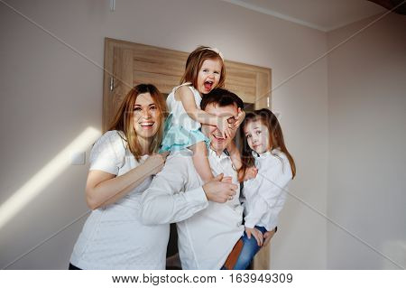 Cheerful family of four people. Young man holding in his arms his two daughters. Pregnant wife nestles on husband. Little girl closes her father's face with her hands. All great fun.