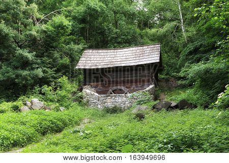 Old abandoned mill stands on a glade surrounded by birch forest. Stones lie around the mill the glade overgrown with nettles