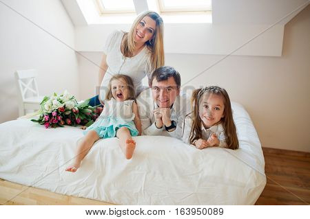 Big cheerful family has settled down on a bed. Father pregnant mother and two little daughters. In a family some holiday. Beautiful bouquet of tulips lies on a bed.