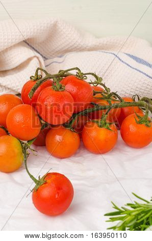 Organic cherry tomatoes with rosemary on wrinkled paper