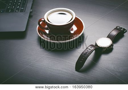 Cup of coffee on a dark table. Concept of business. Laptop, coffee, watch.
